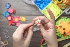 Kind-` s übergibt spinnendes Handwerk der Nahaufnahme von farbigen Gummis, von der Bildung und von der Unterhaltung lizenzfreies stockbild