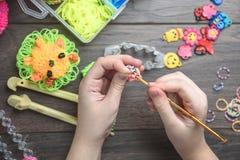 Kind-` s übergibt spinnendes Handwerk der Nahaufnahme von farbigen Gummis, von der Bildung und von der Unterhaltung stockfotos