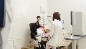 Kind-` s Augenheilkunde - Optometriker in der Klinik kleines Mädchen ` s Vision überprüfend lizenzfreie stockbilder