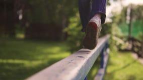 Kind-` s Beinnahaufnahme das Kind ist auf der Querlatte und den Balancen in der Luft das Konzept von einem glücklichen und ein ru