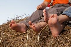 Kind-` s Füße im Heu Stockfoto