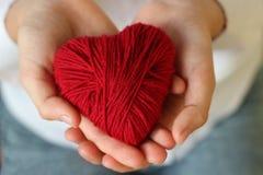 Kind-` s Hände halten ein Herz des roten Threads für das Stricken Valent stockbild
