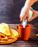 Kind-` s Hände, welche die Milch gießen Pfannkuchen auf einem Brett in der Nähe W Stockfotografie