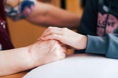 Kind-` s Hand auf eine ältere Frau ` s Hand Lizenzfreies Stockbild