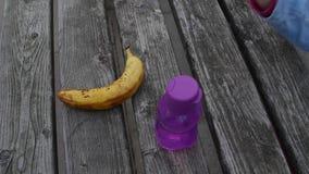 Kind` s hand die organische banaan van zwart-witte strepenachtergrond nemen Hoogste mening Frans die croissant op wit wordt gedie stock videobeelden