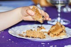Kind-` s Hand, die Stück des Kuchens trägt lizenzfreie stockbilder