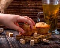 Kind-` s Hand nimmt den Bananenkleinen kuchen Eine Tasse Tee im Ba Lizenzfreie Stockbilder