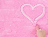 Kind-` s Hand zeichnet ein Herz auf dem dekorativen Sand Stockfoto