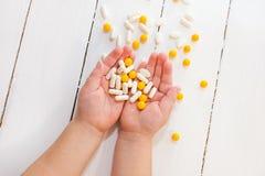 Kind` s handen die pillen en vitaminen houden stock foto's