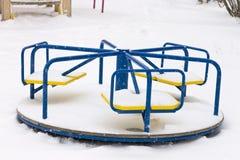 Kind-` s Karussell bedeckt im Schnee auf Spielplatz im Winter Lizenzfreies Stockbild