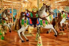 Kind-` s Karussell in einen Vergnügungspark mit den bunten Pferden verziert mit glühenden Glühlampen lizenzfreie stockfotografie