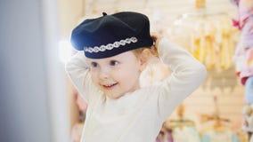 Kind-` s Kleiderspeicher - kleines blondes Baby, das Einkaufs- und des Kaufenshübschen Hut tut Lizenzfreies Stockfoto