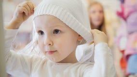 Kind-` s Kleiderspeicher - kleines blondes Baby mit der Mutter, die Einkaufs- und Kaufenhut tut Stockbilder