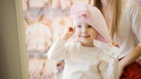 Kind-` s Kleiderspeicher - kleines blondes Baby mit der Mutter, die Einkaufs- und Kaufenhut tut Stockbild