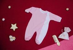 Kind-` s Kleidung mit Spielwaren auf einem Kirschhintergrund Stockfotos