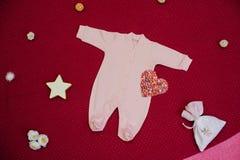 Kind-` s Kleidung mit Spielwaren auf einem Kirschhintergrund Lizenzfreies Stockfoto