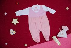 Kind-` s Kleidung mit Spielwaren auf einem Kirschhintergrund Stockfoto