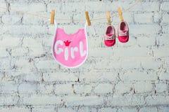 Kind-` s Kleinkind-Rosaspeichel und rote Schuhe auf einem Seil gegen eine weiße Backsteinmauer Stockfotos