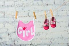 Kind-` s Kleinkind-Rosaspeichel und rote Schuhe auf einem Seil gegen eine weiße Backsteinmauer Stockfoto