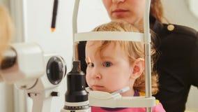 Kind` s optometrie - meisje hecks zicht in oog oftalmologische kliniek stock foto's