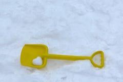 Kind-` s Schaufel liegt auf dem weißen Schnee Im Blatt liegt ein Schneeball in Form eines Herzens Stockfotografie