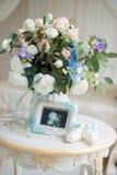 Kind-` s Schuhe und Ultraschall des Baby ` s Fötusses mit einem schönen Blumenstrauß von Blumen Stockbild