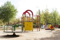 Kind-` s Spielplatz im Hof des Hausschwingens, Dias Stockfoto