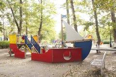 Kind-` s Spielplatz im Hof des Hausschwingens, Dias Lizenzfreie Stockfotografie