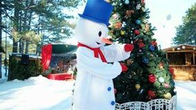 Kind-` s Trickzeichnerschneemann, tanzender Schneemann, lustiges Manntanzen im Abendkleid auf dem Hintergrund des Weihnachtsbaums stock video