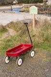 Kind ` s Weinig Rode Wagen bij de rand van een Strand en van de Strandtoegang Teken stock afbeeldingen