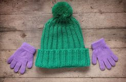 Kind-` s Winterzubehör: Hut und Handschuhe Rustikales hölzernes BAC Lizenzfreie Stockfotografie
