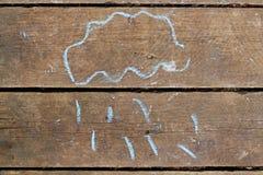 Kind-` s Zeichnung der Wolke mit dem Regen gezeichnet mit Kreide auf alten hölzernen Planken Lizenzfreies Stockbild