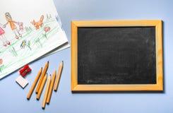 Kind-` s Zeichnung, farbige Bleistifte und Kreidebrett Stockbilder