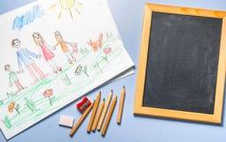 Kind-` s Zeichnung, farbige Bleistifte und Kreidebrett Lizenzfreie Stockfotos