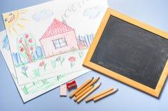 Kind-` s Zeichnung, farbige Bleistifte und Kreidebrett Stockfoto