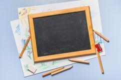 Kind-` s Zeichnung, farbige Bleistifte und Kreidebrett Stockfotos