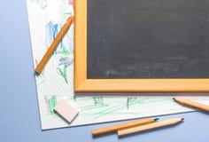 Kind-` s Zeichnung, farbige Bleistifte und Kreidebrett Lizenzfreies Stockbild