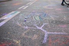 Kind-` s Zeichnung mit Kreide auf einer Pflasterung Stockfotografie