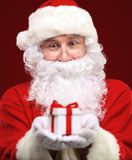 Kind Santa Claus giving xmas present Stock Photography