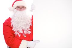 Kind Santa Claus pointing in white blank sign, isolated on white background.  Royalty Free Stock Photo