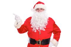 Kind Santa Claus pointing in white blank sign, isolated on white background.  Royalty Free Stock Images