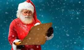 Kind Santa Claus reading vintage paper with wishes. Stock Photography