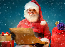 Kind Santa Claus with vintage list and gifts on blue background royalty free stock images