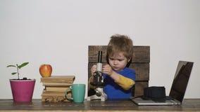 Kind, Schüler mit lächelndem Gesicht die Arbeit eines Mikroskops studierend Kinderjunge interessiert an dem Studieren, Ausbildung stock footage