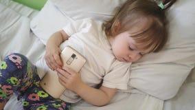 Kind schläft auf Kissen und hält eine Tablette Nettes Baby, das im Bett mit Smartphone schläft lizenzfreie stockfotografie