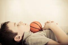 Kind schlafend mit wenigem Ball unter Kinn lizenzfreie stockfotografie