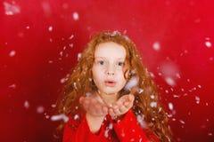 Kind in Schlagschnee des weißen Hutes mit ihrer Hand Stockbilder