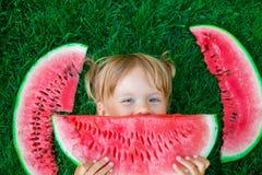 Kind schließt ihre Lippen durch die Scheibe der Wassermelone und liegt auf dem Gras im Sommer glücklich Stockfotografie