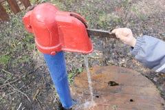 Kind schließt Wassersäule mit ein Spalte mit Trinkwasser, das Kind Stockbild