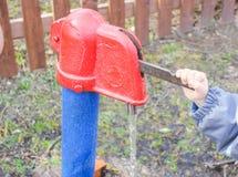 Kind schließt Wassersäule mit ein Spalte mit Trinkwasser, das Kind Lizenzfreie Stockfotos